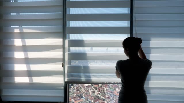 kobieta otwiera rolety, patrząc na okno z panoramicznym widokiem na miasto i rozciąganiem. - store filmów i materiałów b-roll
