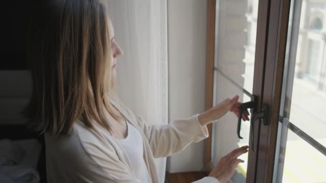 vídeos de stock e filmes b-roll de woman is opening window in room and breathing air - open window
