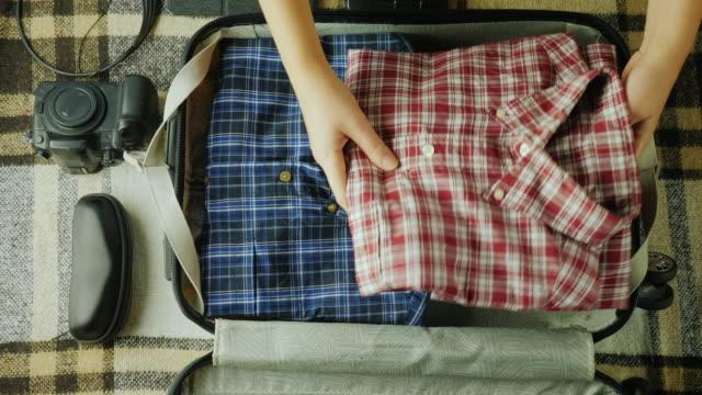 stockvideo's en b-roll-footage met een vrouw is het inpakken van een koffer. het zet dingen samen voor reizen - ingepakt