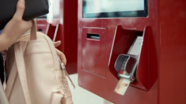 Woman is paying by card in automat, close-up of hands Girl buyer is inserting bank card in payment automat. She is putting pin code, taking off a bill, waiting an order banks and atms stock videos & royalty-free footage