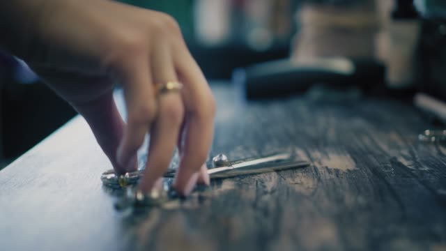 Woman is putting hairdresser's scisors on table in hair salon. Closeup view video