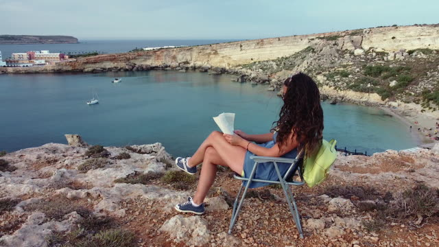 Woman is reading a book on cliff with beautiful view