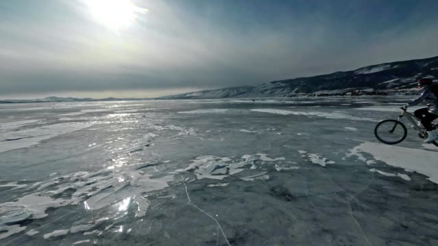 Woman is riding bicycle on the ice. The girl is dressed in a silvery down jacket, cycling backpack and helmet. Ice of the frozen Lake Baikal. The tires on the bicycle are covered with special spikes.