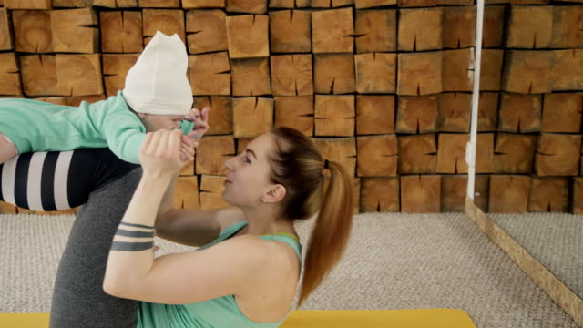 A woman is rocking a press on her stomach during fitness with a baby. Mom holds a child on her lap, feet on the floor video