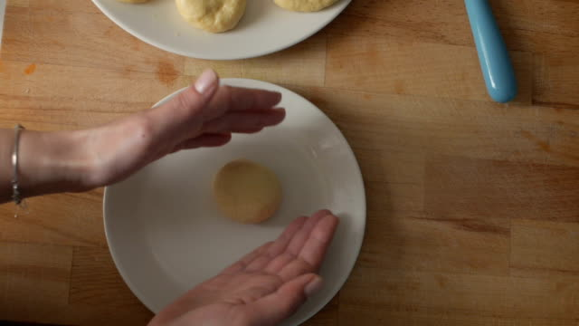 Woman is rolling the dough stuffed with delicious fillings
