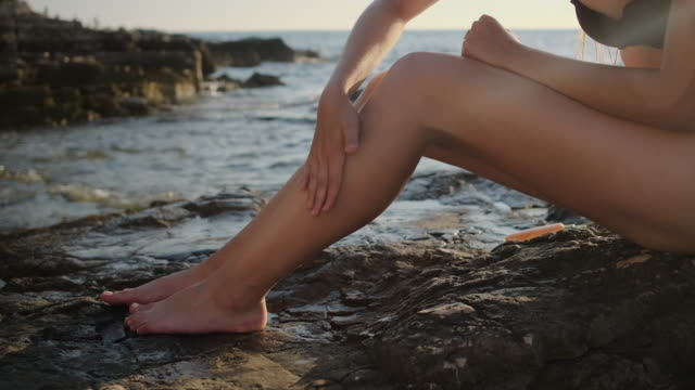 woman is rubbing sunscreen cream in skin of legs, sitting on sea beach - vídeo