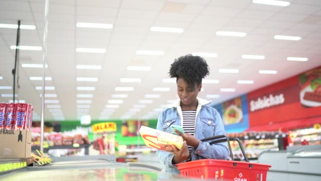 Woman is shopping in supermarket and scanning barcode with smartphone