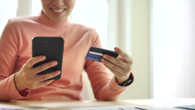 Woman is shopping online using a smartphone at home