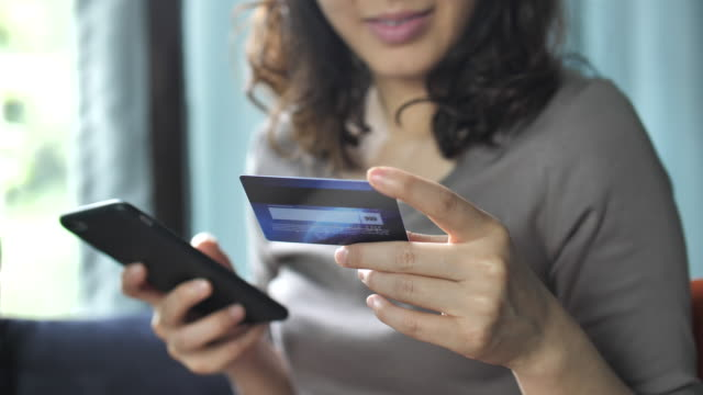 Woman is shopping online using a smartphone Woman is shopping online using a smartphone credit card purchase stock videos & royalty-free footage