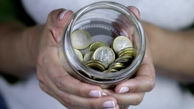 Woman is showing European Union Money in Jar