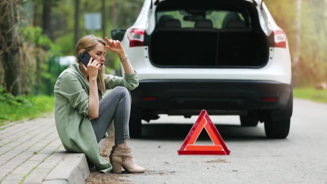 woman is sitting on the side of the road and calling for help because broken car