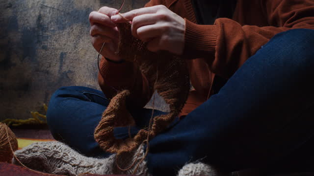 Woman is sitting on the sofa and knitting. Low section view