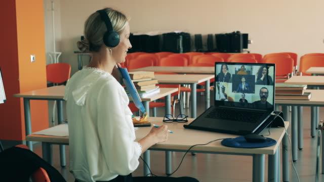 во время виртуального урока женщина разговаривает с несколькими пользователями. дистанционное образование, онлайн-урок колледжа, концепц� - дистанционный стоковые видео и кадры b-roll