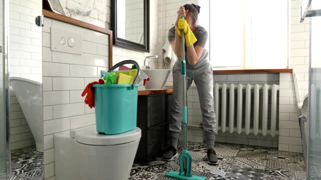woman is tired to cleaning tile in toilet - addetto alle pulizie video stock e b–roll