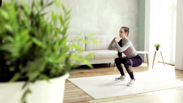 kvinna tränar gör knäböj och utfall hemma i vardagsrummet, sidovy - hemmaträning bildbanksvideor och videomaterial från bakom kulisserna