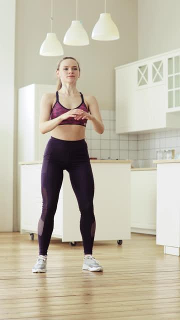 vídeos de stock e filmes b-roll de woman is training making squats exercises at home, vertical video, front view - treino em casa