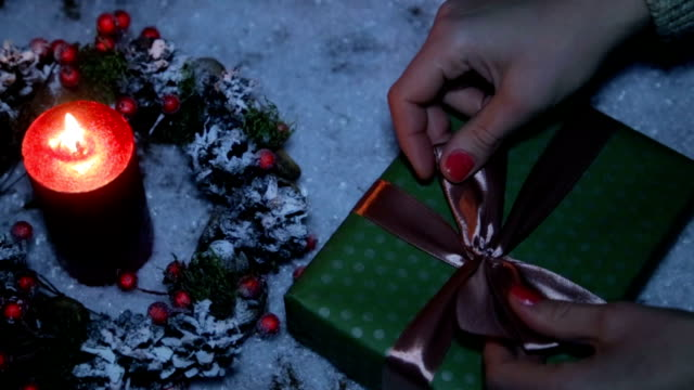 a woman is tying a bow on a christmas present - nastro per capelli video stock e b–roll