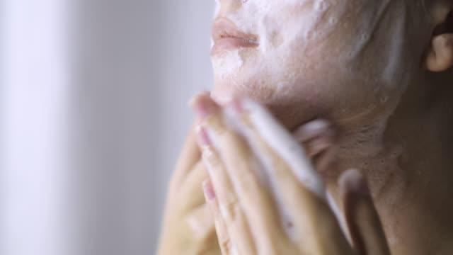 la donna sta lavando il viso per la pulizia con detergente organico schiumoso, vista ravvicinata. - gommapiuma video stock e b–roll