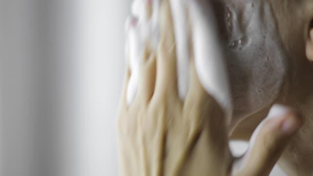 la donna sta lavando il viso di pulizia con sapone espanso organico, vista laterale ravvicinata. - gommapiuma video stock e b–roll