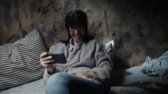 Woman is watching a funny video by her smart phone video
