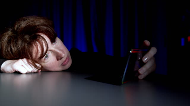 A woman is watching her smartphone while having her head lying on the table video