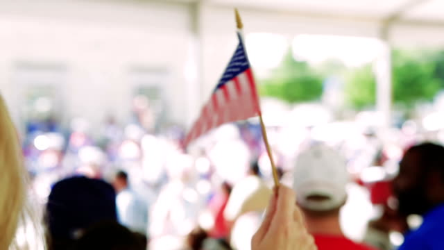 Woman is waving American flag during Fourth of July parade Caucasian woman with blonde hair is standing in crowd on sidewalk and is waving a small American flag. She is attending a parade to celebrate the Fourth of July Independence Day holiday, and is celebrating American patriotism. fourth of july videos stock videos & royalty-free footage