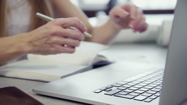 stockvideo's en b-roll-footage met de vrouw werkt met laptopzitting bij lijst die informatie van notitieboekje controleert - hand pointing