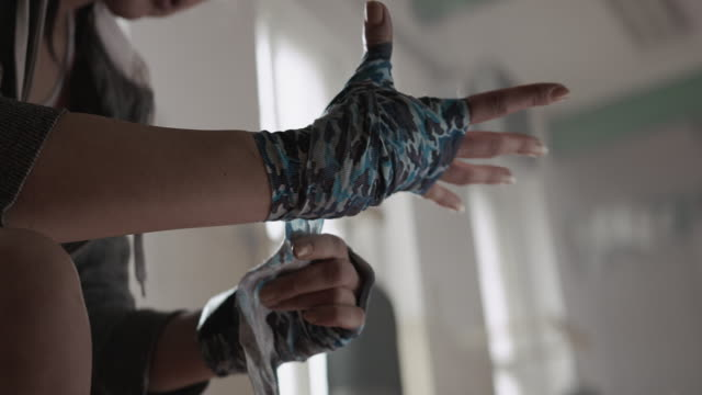 Woman is wrapping hands with boxing wraps Female boxer is wrapping hand with tape before training. She's sitting on a bench in a training hall. Camera Arri Alexa with Anamorphic Lenses. 60fps wrapped stock videos & royalty-free footage