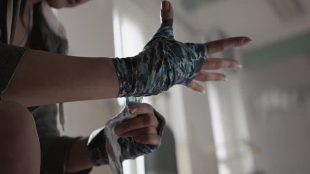 Mujer se resumen las manos con envolturas de boxeo - vídeo