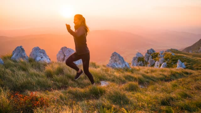 Woman jogger running in mountains at sunset Young body conscious woman jogger running in mountains at sunset athleticism stock videos & royalty-free footage