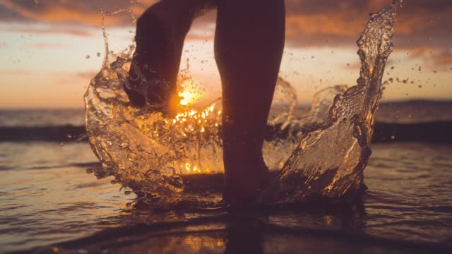 vídeos de stock e filmes b-roll de copy space: woman jogger splashes water by running into the ocean at sunrise. - descalço