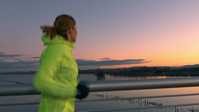 vídeos de stock e filmes b-roll de slo mo woman jogging across the bridge at sunset - roupa desportiva