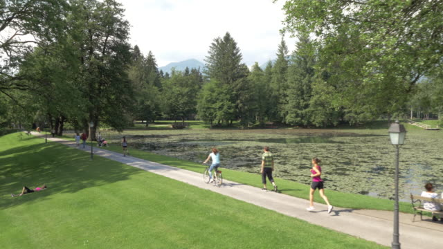 aerial woman jogging along a lake in a busy park - bench stock videos & royalty-free footage