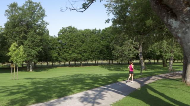 vídeos de stock e filmes b-roll de antena mulher jogging ao longo de um lago no parque - 25 29 anos