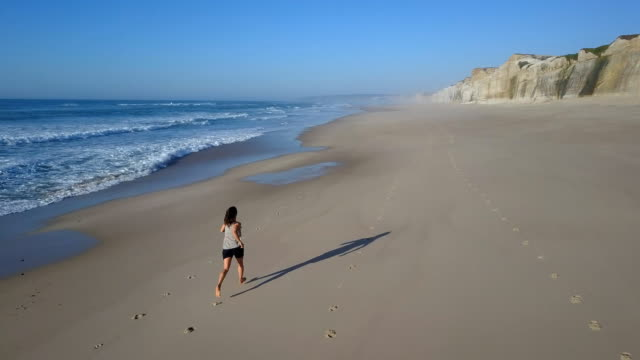 Woman jogging along the beach back view video