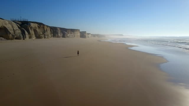 stockvideo's en b-roll-footage met vrouw joggen langs het strand fly away - portugal