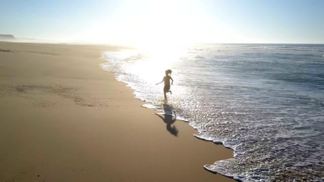 Woman jogging along the beach water splash