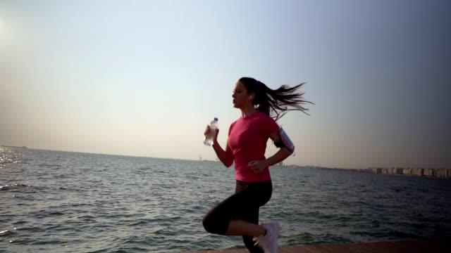 frau joggt am meer - freizeitaktivität im freien stock-videos und b-roll-filmmaterial