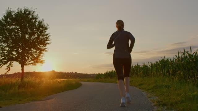vidéos et rushes de slo mo femme jogging dans la campagne au coucher du soleil - joggeuse