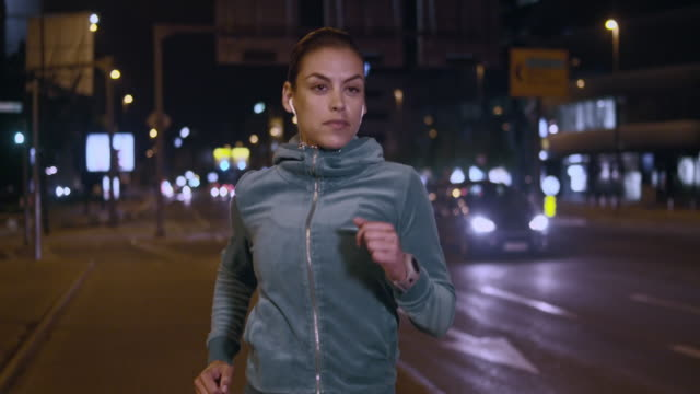 SLO MO TS Woman jogging in the city street at night video