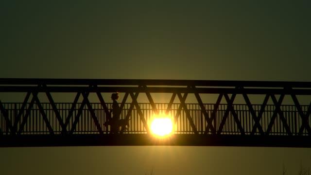 en kvinna joggade över en bro vid solnedgången med sin hund. - pet bottles bildbanksvideor och videomaterial från bakom kulisserna