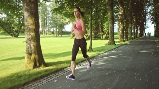 SLO MO TS Woman jogging through a tree-lined lane listening to music video