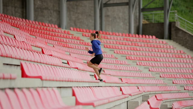 Woman jogging up stairs. Steadicam stabilized shot. Sportswoman wearing barefoot sports shoes while training on the stairs. video