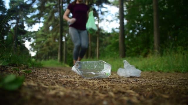 Woman jogging with garbage bag