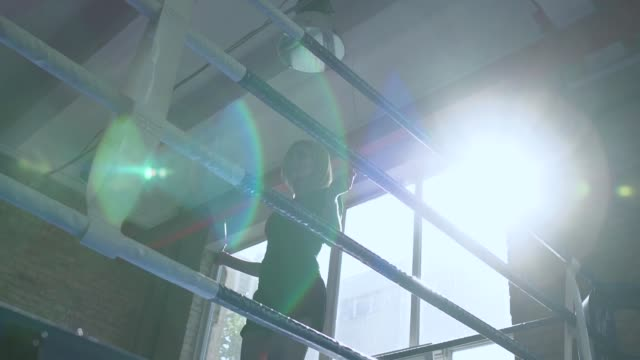 Woman jump at skipping rope at boxing ring against the sun video