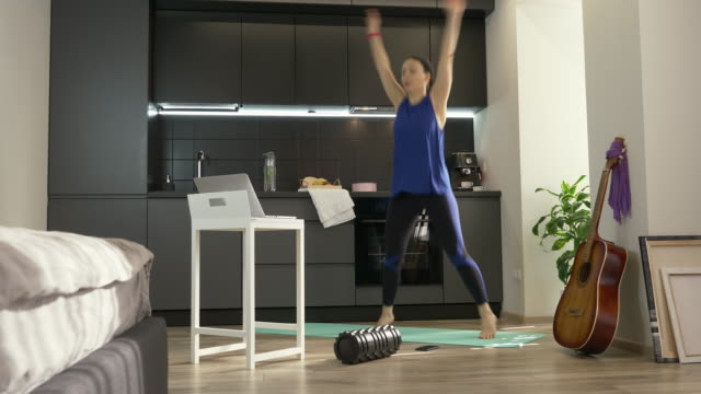 vídeos de stock e filmes b-roll de woman jumping and doing fitness aerobic exercises at home in kitchen using online training app on laptop computer. fit sporty girl in athletic sportswear doing morning sport excersises at home - treino em casa