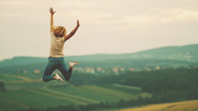 MS Woman jumping for joy in rural field Woman jumping for joy in rural field. Slow Motion. jumping stock videos & royalty-free footage