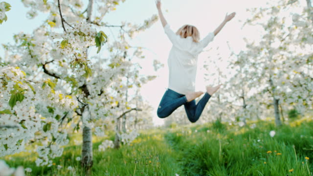 vídeos de stock e filmes b-roll de slo mo woman jumping in joy among cherry blossoms - mês