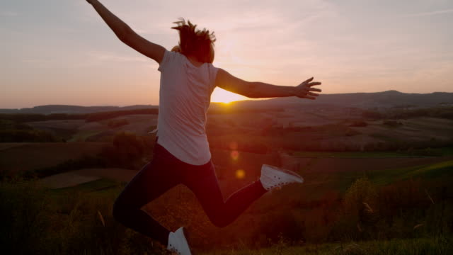 vídeos de stock e filmes b-roll de slo mo woman jumping in joy at sunset - braços no ar