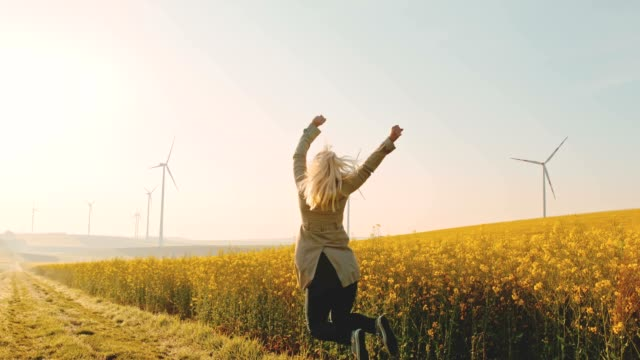 SLO MO Woman jumping in joy next to a canola field with wind turbines in the distance video